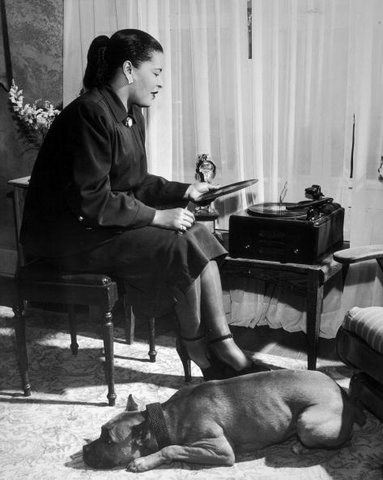 vintageblackglamour :      Billie Holiday playing records and hanging out with her dog Mister circa 1945. Photo by Metronome/Getty Images.