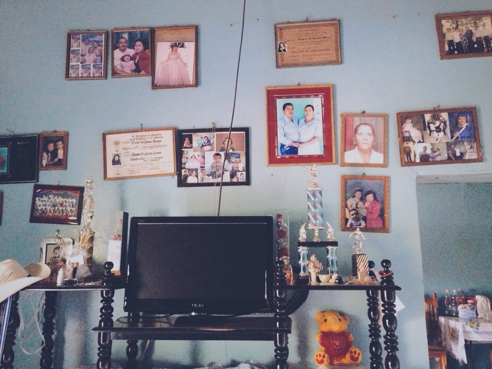 "Cada hogar en este pulgarcito de este país tiene una pared cómo ésta. Fotos de los hijos grandes, nietos lejanos, padres fallecidos, títulos de bachillerato y retratos formales estremece la paredes como una muralla de familia. ""Estas son la gente que hemos querido. Estos son nuestra familia,"" declaran los cuadros juntos.         Every home in this pulgarcito of a country has a wall like this one. Pictures of grown children, distant  grandchildren, deceased parents, high school degrees, and formal portraits scatter the plaster as a family mural. ""These are the people we have loved. This is our family,"" the frames proclaim in unison."