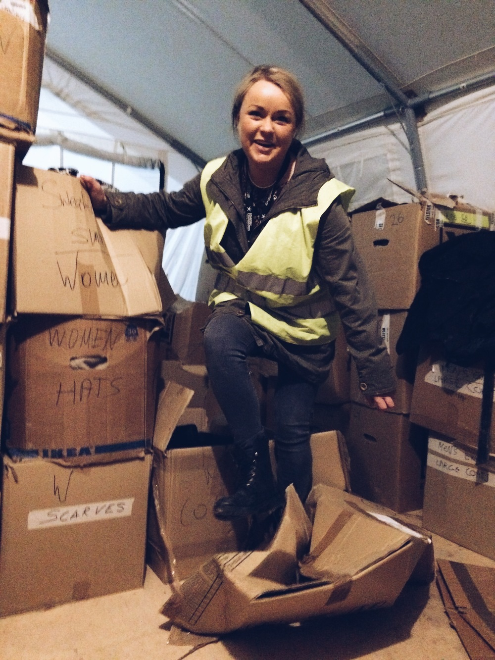 Jenny, a volunteer since October, taking revenge on the empty boxes of the men's clothing tent, IRC Camp.