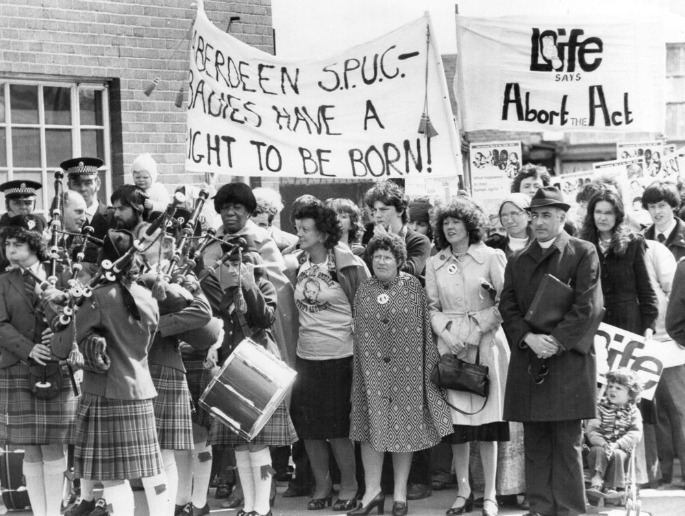 Speakers and supporters marching prior to an anti-abortion rally held   in Dundee, Scotland, on 22nd April, 1979. Speakers and supporters   pictured are (from left to right), Mrs Emma Clardy Craven, a black   American human rights worker, a Methodist, and Chairman of the Human   Rights Commission in Minnesota, US; Dr Margaret White, a general   practitioner, author, speaker and broadcaster, and former vice-president   of SPUC; Marilyn Gillies Carr, a pro-life lady born without arms who   spoke out for the right to life of the disabled; Marysia Kobylarska, who   is now the chairman of SPUC Dundee; and Archbishop Conti, then Bishop   Conti, the bishop of Aberdeen.