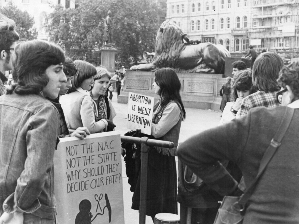 "A Pro-Life witness in Trafalgar Square, London, in   1976, led by The Survivors, a pro-life theatre group. The Survivors was   established in 1975 by John Smeaton, now the chief executive of the   Society for the Protection of Unborn Children, and Debby Sanders, who   was the leader of Women for Life, a pro-life feminist group. The   Survivors performed at the Edinburgh Fringe Festival in 1975 in a revue   entitled ""I'm a Product of Conception - Aren't We All?"""
