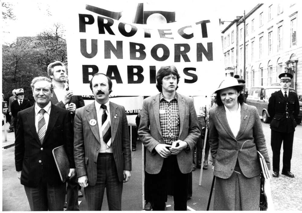 Mary Kenny, the Irish author, playwright, broadcaster and journalist,   joins a Call for Action pro-life march and rally held in Glasgow on 31st   October 1976, organised by the Society for the Protection of Unborn   Children. Also picture, second on the left, is Ian Murray, formerly   director of SPUC Scotland and SPUC general secretary. The rally in   Glasgow was one of a number of regional marches and rallies held around   Britain, including Bristol, Chelmsford, and Birmingham. The rallies were   held to call on Parliament to take action to stop abortion