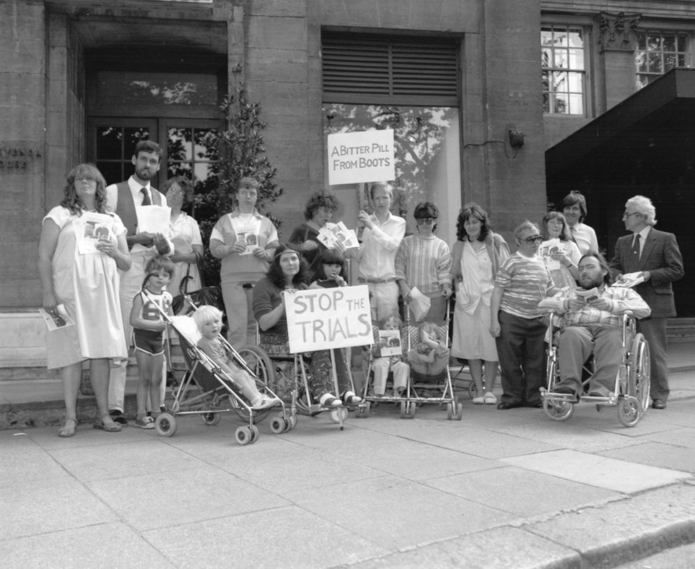 "In 1983, SPUC No Less Human, then known as the disabled division of   the Society for the Protection of Unborn Children, led by Alison Davis   (pictured, centre, with the Stop the Trial banner), ran a campaign to to   ry to stop the Medical Research Council trials in which some mothers   would deliberately be allowed to become pregnant with disabled babies.   SPUC's protest targeted Boots which was providing pills for the project.   Mothers would be screened and if the baby was found to be disabled they   would be offered an abortion ""to get rid"" of the baby."