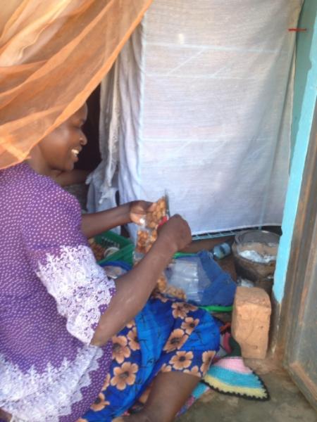 """Faith packaging """"Daddies"""" a popular Ugandan snack she sells near Entebbe, Uganda."""