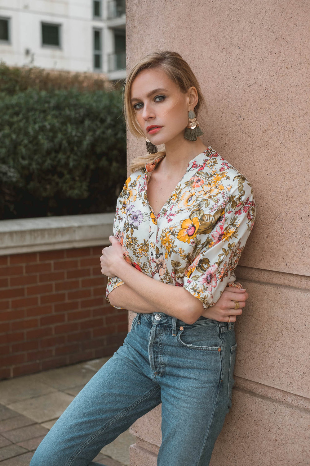 Annabell is wearing a   Zara blouse  , High waist jeans by   Agolde   and tassel earrings by   H&M