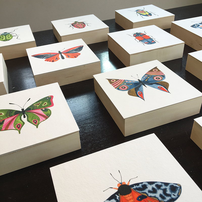"Entomology series by Misha Zadeh. 12 original 6""x6"" acrylic ink paintings with gold detailing on watercolor paper, mounted on 1.5"" wood panels. Each fantastical insect is paired with a positive trait like 'compassion', 'integrity', 'wit','humility'."
