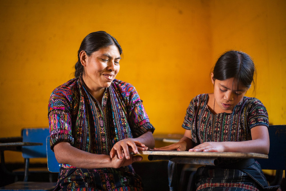 Indigenous Kaqchikel student Aracely Lec reads to her mother in a rural public school of Sololá, Guatemala. Photo for Child Aid.