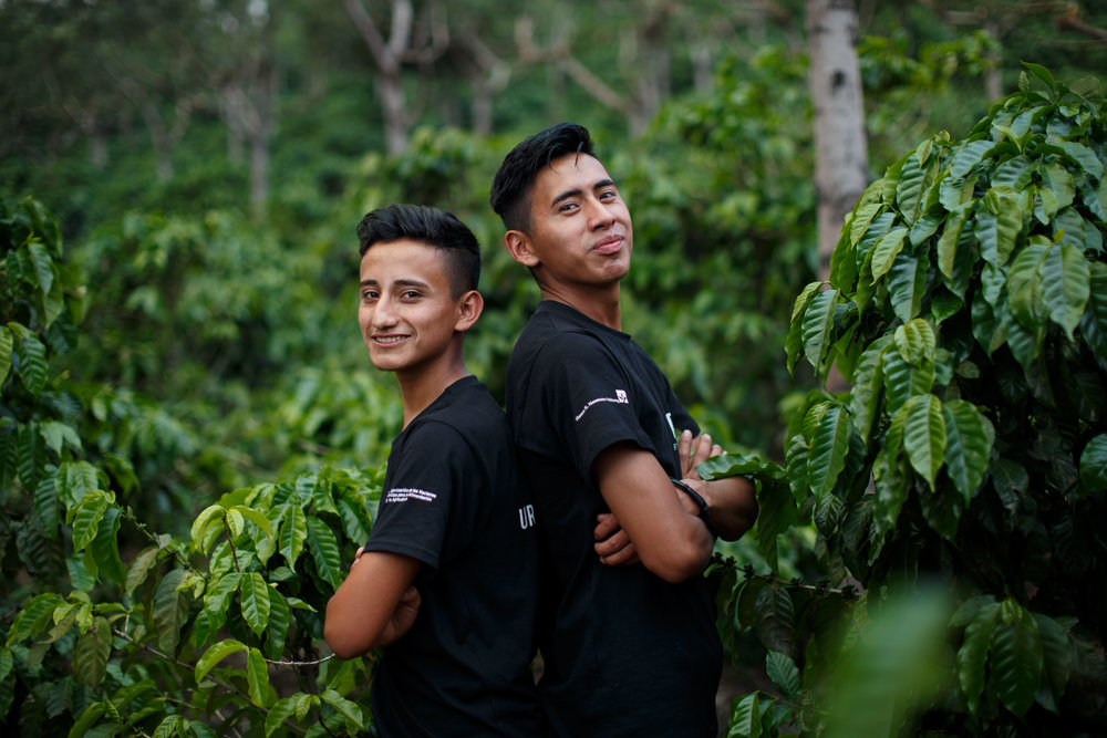 Future coffee farmers pose proudly in a coffee farm during an event that links youth from rural, remote areas of Guatemala with coffee producers, buyers, and baristas. Photo for HRNS Institute.