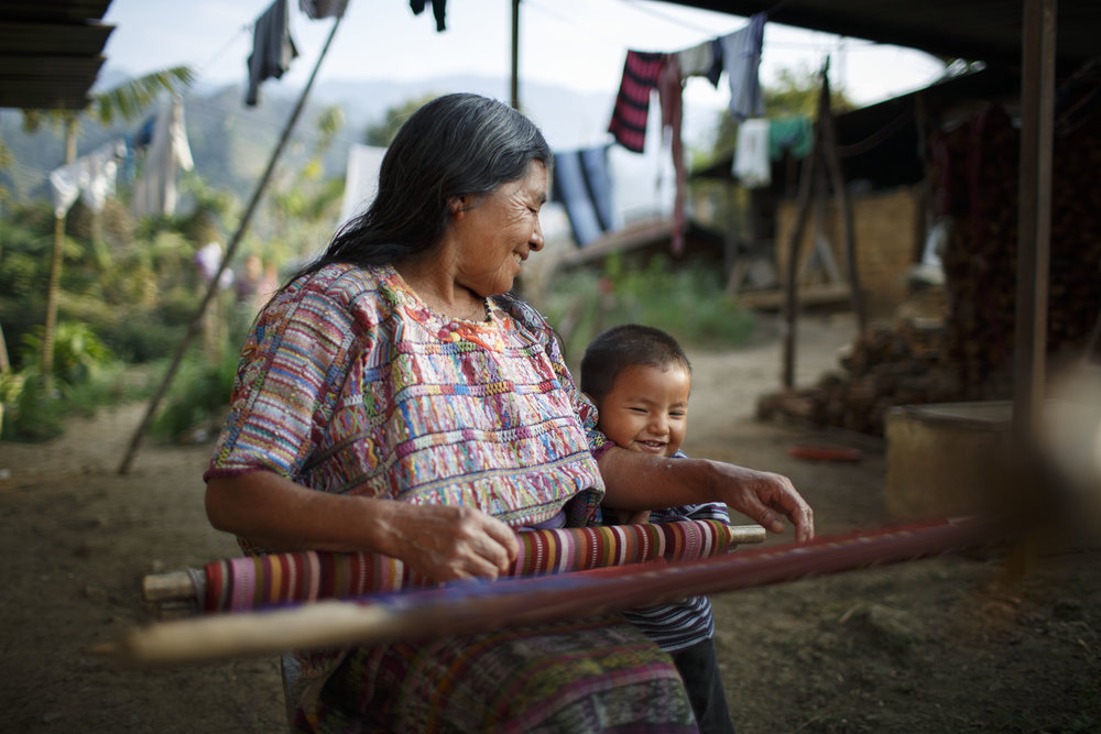 Doña Catalina with her grandson in front of her backstrap loom, outside her home in San Juan Cotzal, Nebaj. Photo for The Fair Wage Project.