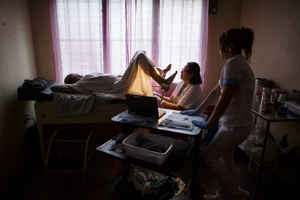 A doctor in a clinic in one of Tegucigalpa's most dangerous neighborhoods removes cancerous lesions from a woman's cervix. Photo for World Health Organization.