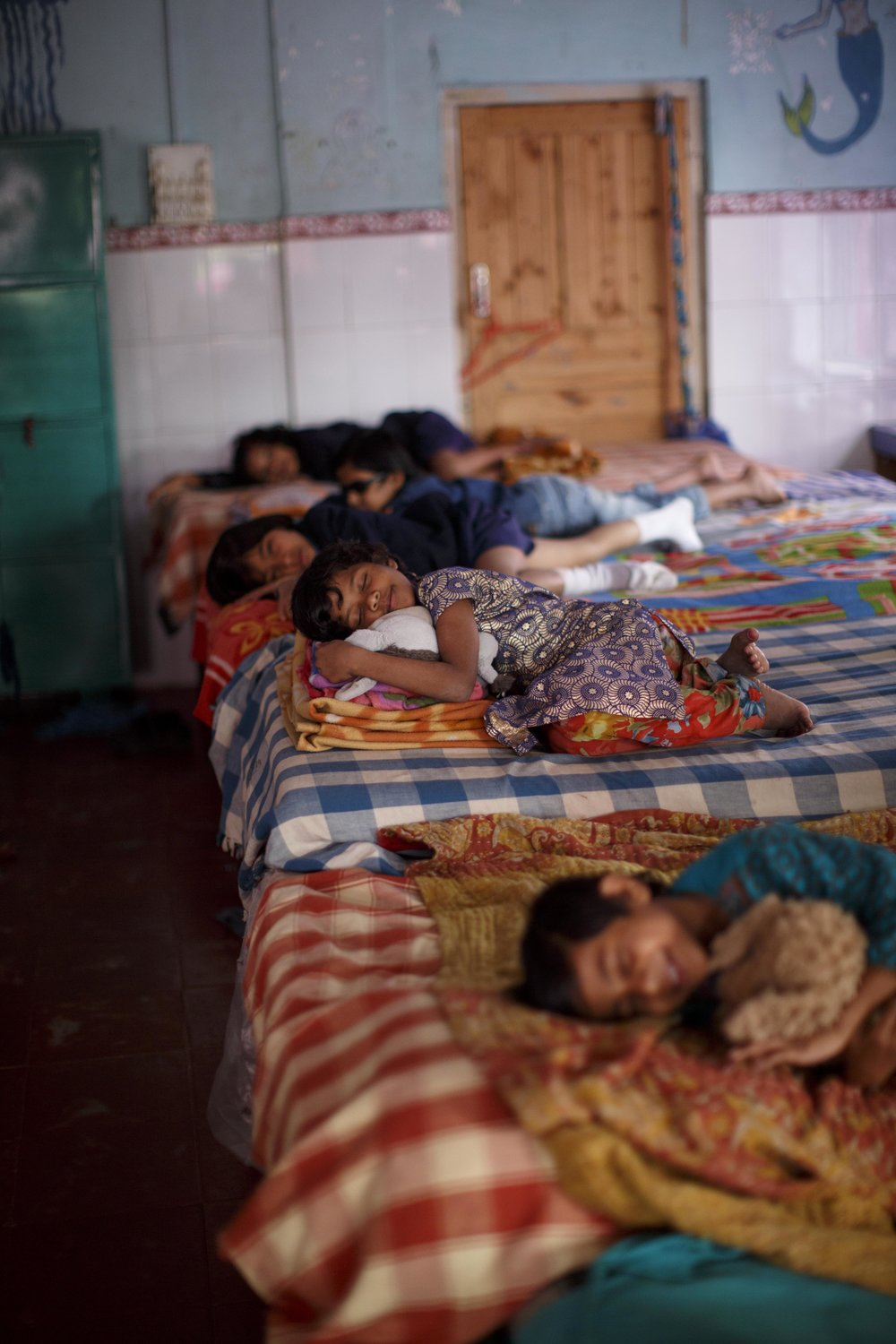 Girls nap after school at a home that provides shelter, education, vocational training, and community for children from the street or disadvantaged homes outside Kolkata, India. Photo for Xavier's Home.