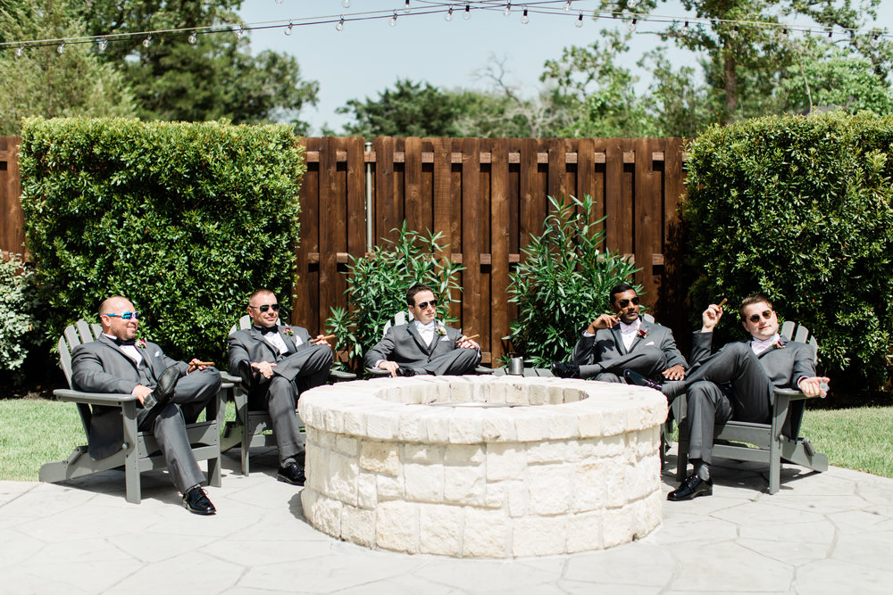 Groomsmen hanging out by firepit before wedding