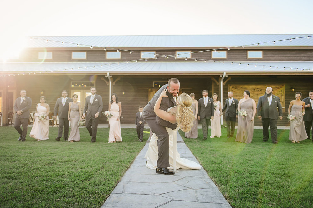 groom dipping bride in front of barn.jpg