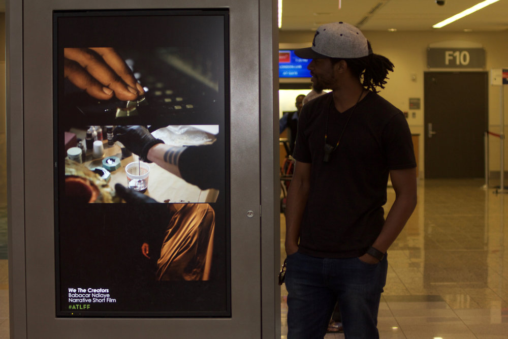 FILMMAKER-IN-RESIDENCE BABACAR NDIAYE PICTURED WITH HIS AIRPORT SHORT, WE THE CREATORS