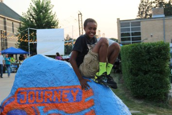 A little boy sits on the Rock welcoming new students.