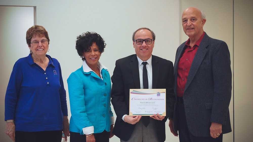 Rancho Cucamonga Mayor Pro Tem Sam Spagnolo, along with Rancho Cucamonga Council Member Lynne B. Kennedy and Rancho Cucamonga Council Member Diane Williams, present Tekton Hospitality's Certificate of Recognition to Henry Savedra Jr, President CEO of Tekton Hospitality
