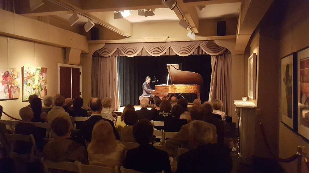 Solo jazz piano and vocals in a relaxed and elegant environment, with a supportive audience.