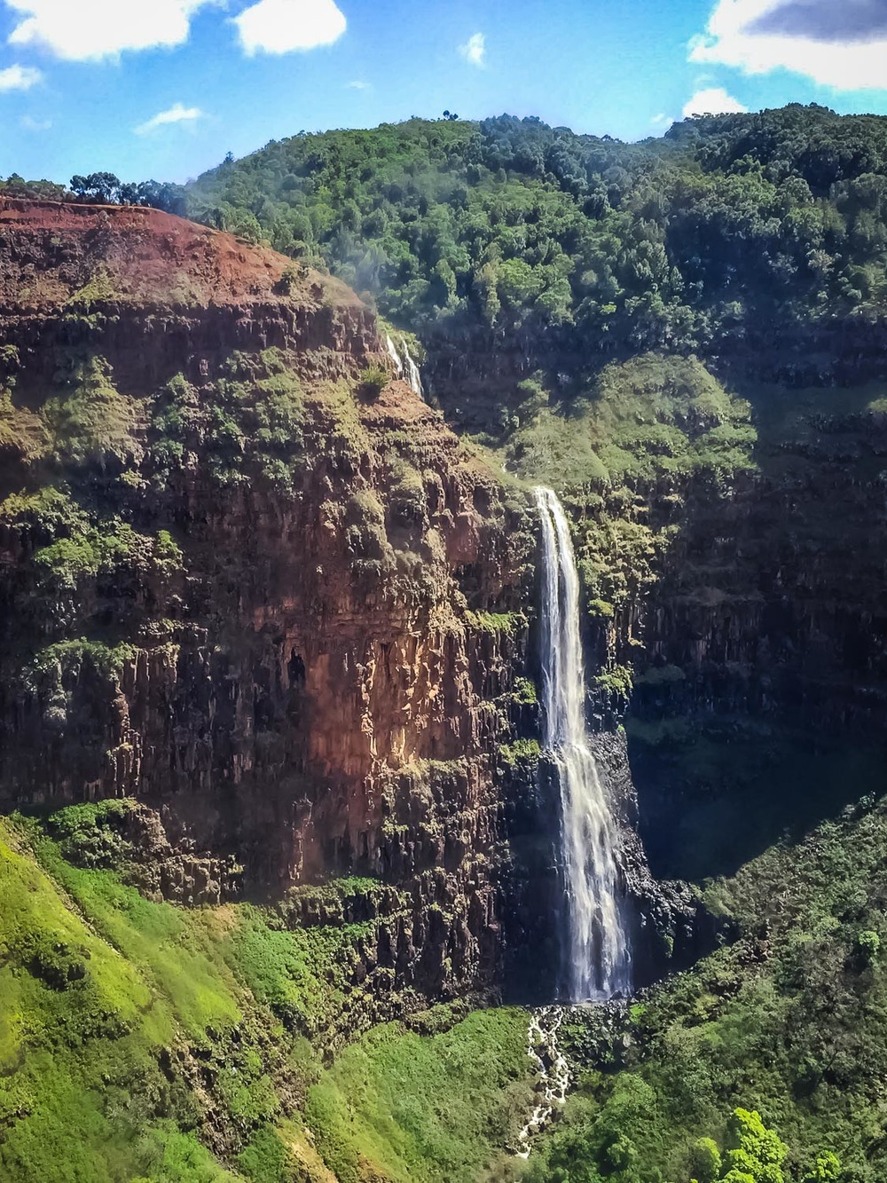 A beautiful view of a waterfall on Kauai's Na Pali Coast during our helicopter tour