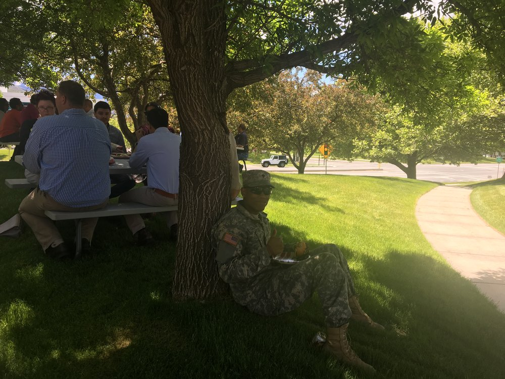 Soldier sitting in the shade enjoying his burger.