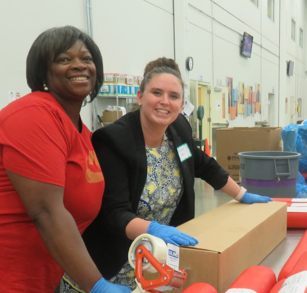 Patricia Quinn (Director of HR) & Brittany Norris (Catering Sales Manager) help box up 36 pounds of bologna! Photo courtesy of the Northern IL Food Bank.