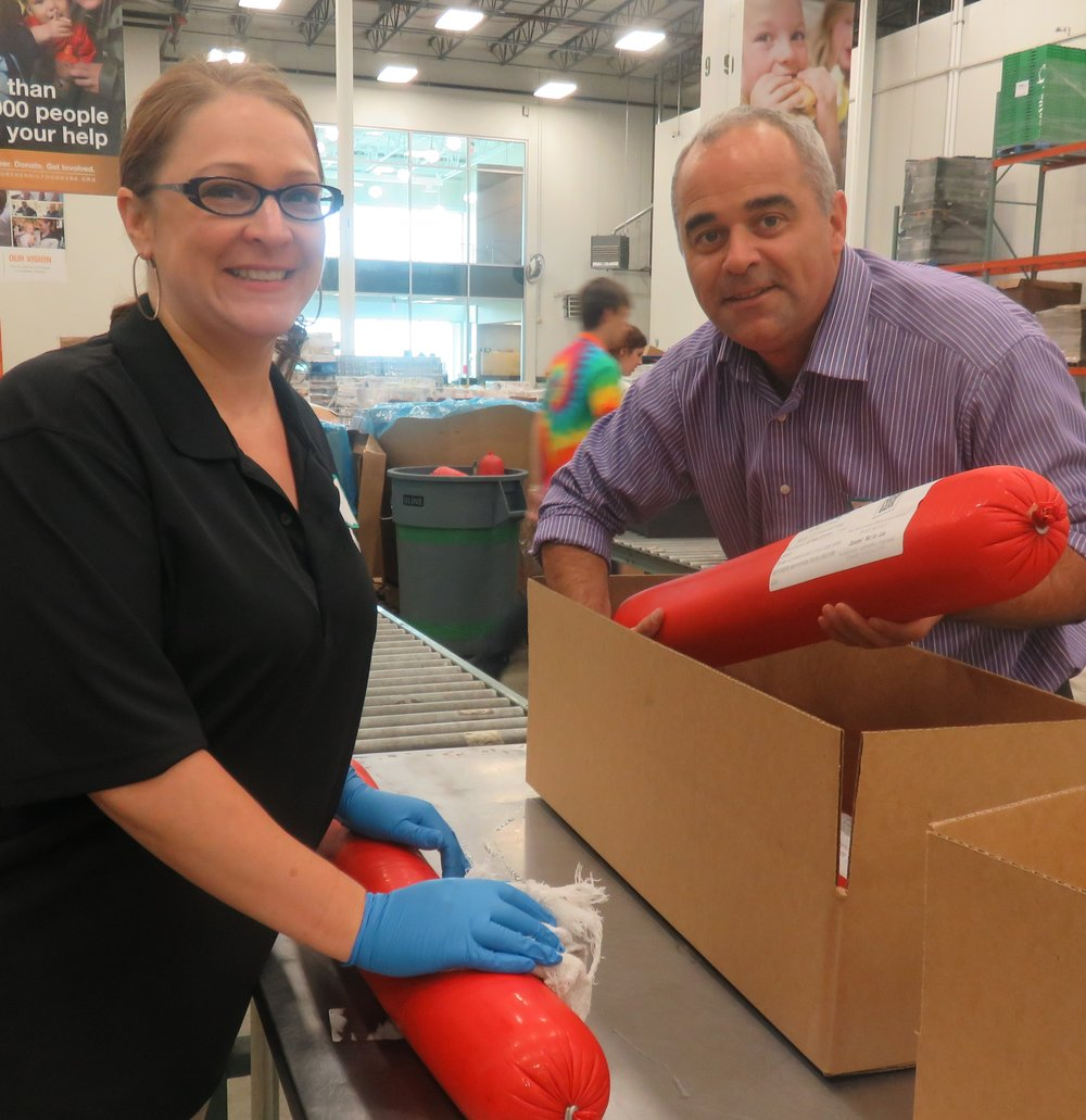 Lisa K. Adams (Marketing Manager) & Mathias Dalbera (Director of Revenue) place labels on bologna before boxing it up. Photo courtesy of the Northern IL Food Bank.