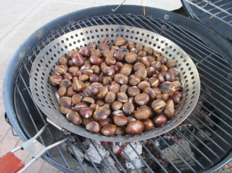 Roasting chestnuts over charcoal. Notice the single slit in the shells across their middles.