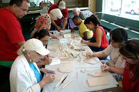 Community members create handmade ceramic tiles in a neighborhood artist's studio for the Living 2007 bricolage.