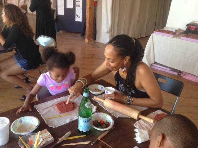 Artist Sonja Henderson assists community members in the creation of tiles for the MLK Living Memorial.