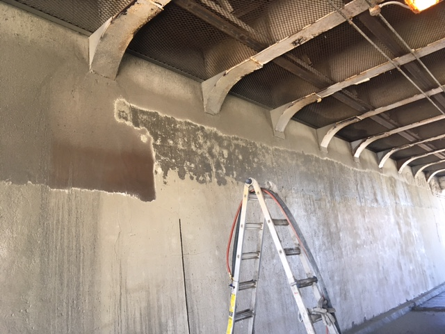 This image shows one of the underpass walls undergoing the sandblasting process in order to prepare the wall for the new mural.