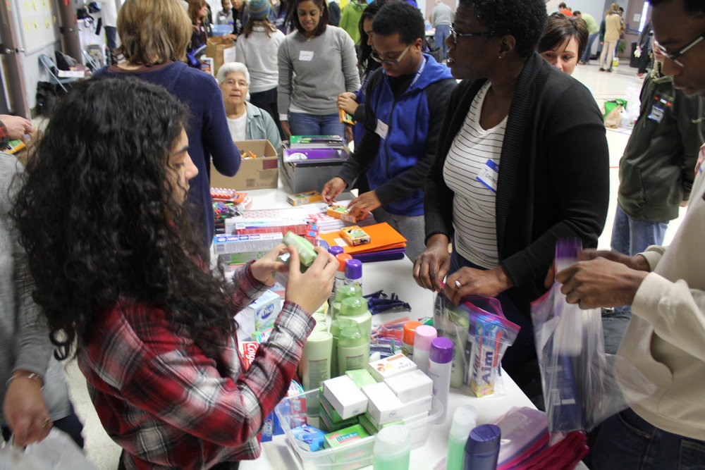 A group assembles toiletry kits for unaccompanied immigrant minor children that LSG Serves
