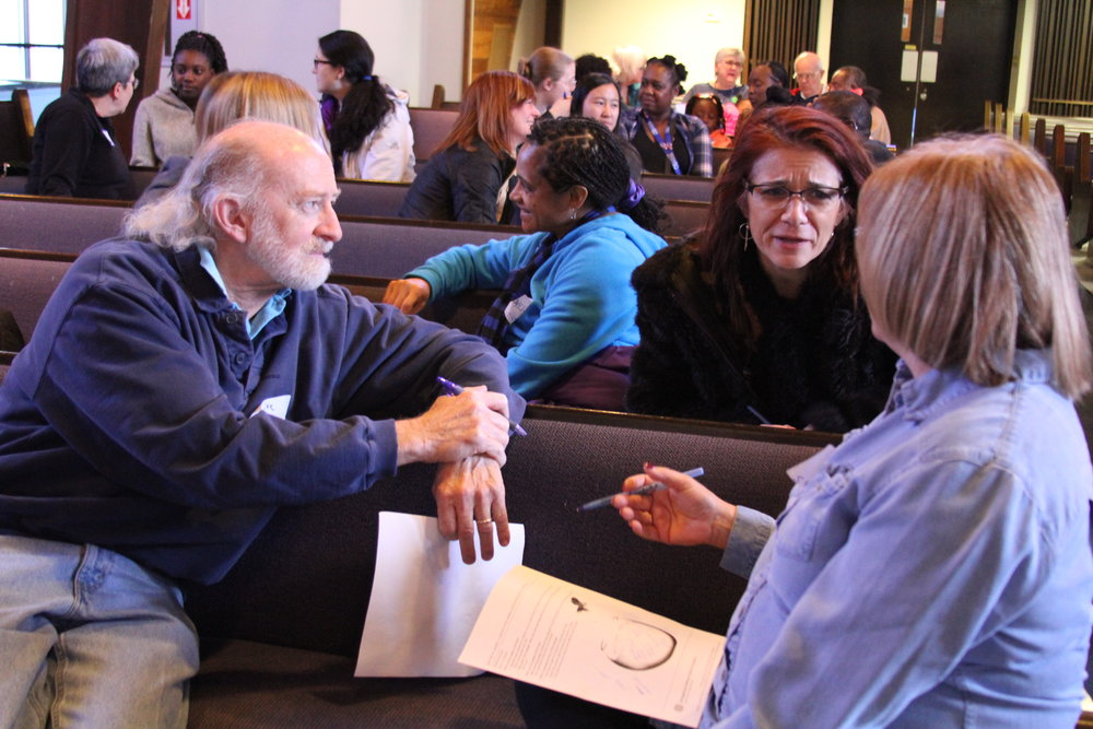 Workshop participants gathered in groups for a learning exercise during the racial justice workshop