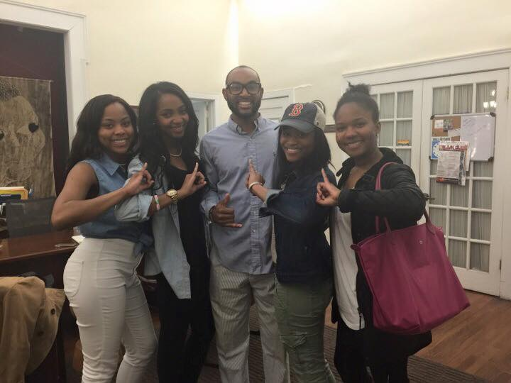 Members of the Lambda Upsilon Chapter posing with Kenny Rice (Alpha Phi Alpha) after an event in Harambee House