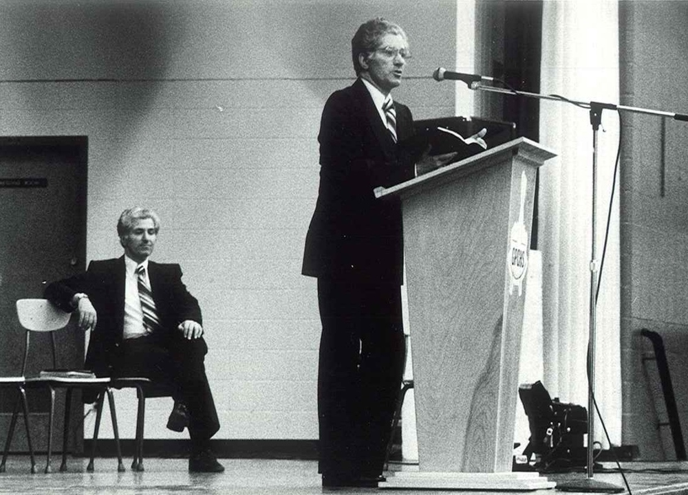 Sutera Twins on stage in a high school auditorium in Grande Prairie, AB with over 1,000 in attendance. (1984)