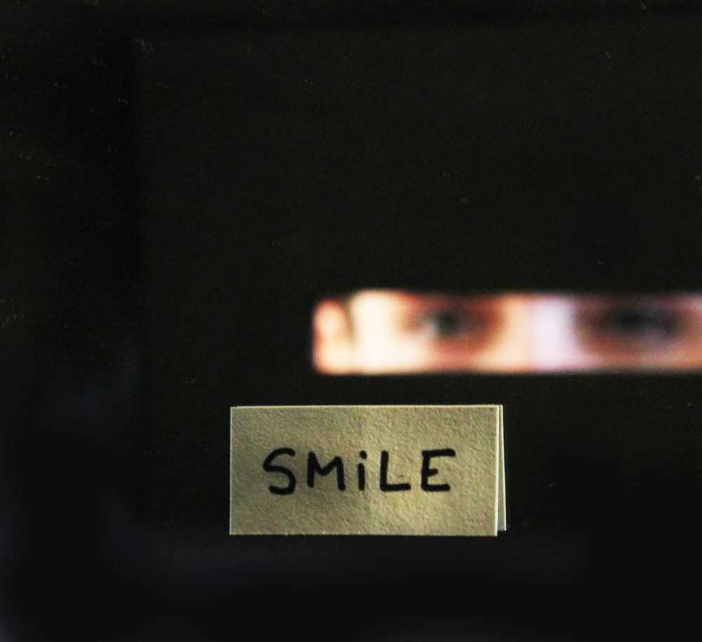Box of smiling eyes, 2014  Closed painted wooden box with a small peephole to look inside the box and see your own eyes reflecting in a mirror and the word SMILE.