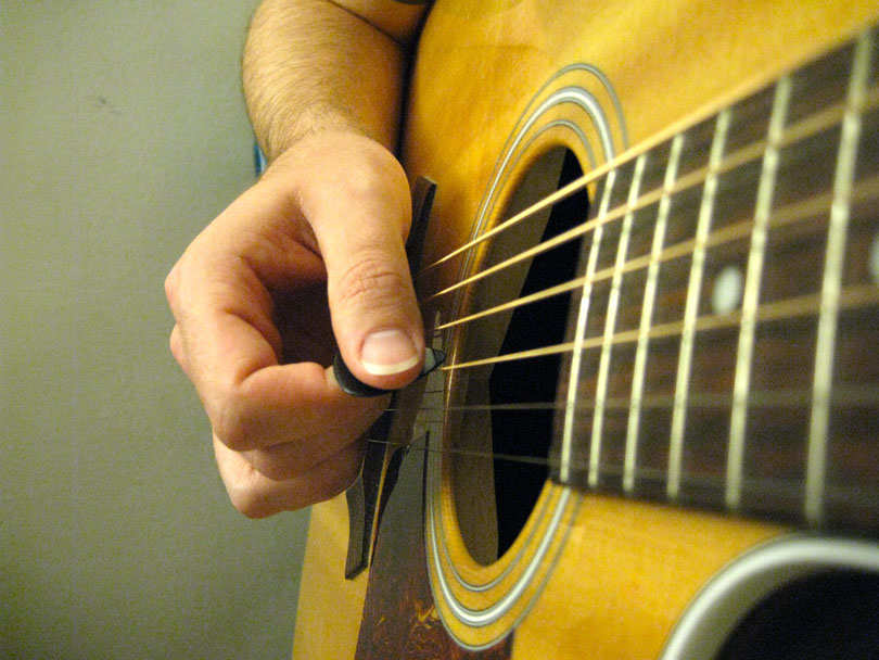 Hold your guitar pick at an angle to the string for a bigger tone.