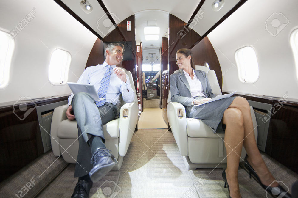 42416697-Smiling-Businessman-and-Businesswoman-with-digital-tablet-having-meeting-in-private-jet-Stock-Photo.jpg