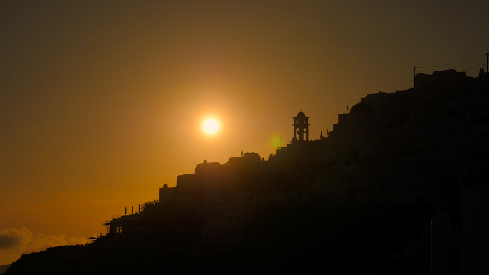 Santorini Wedding Videographer captures the sun setting over the hills.