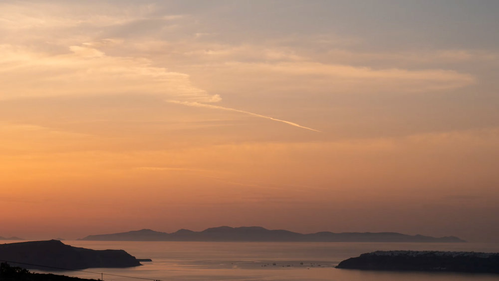 Santorini Wedding Videographer captures stunning sunset from Sara and Gareth's Wedding Reception at Pyrgos Restaurant, Santorini.