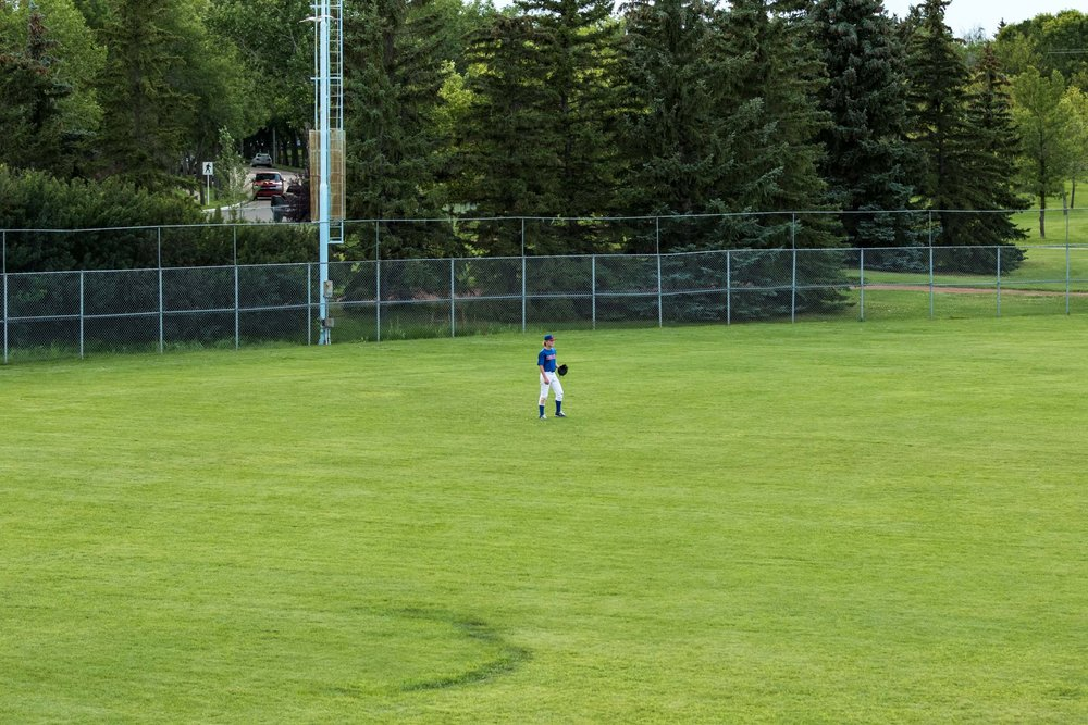 Showcasing the vastness of playing the outfield was what I was trying to capture with this photo. There is a lot of green for one guy to cover and there is often no one behind you to help if you make a mistake | August 6 at Rudy Swanson Park, Camrose