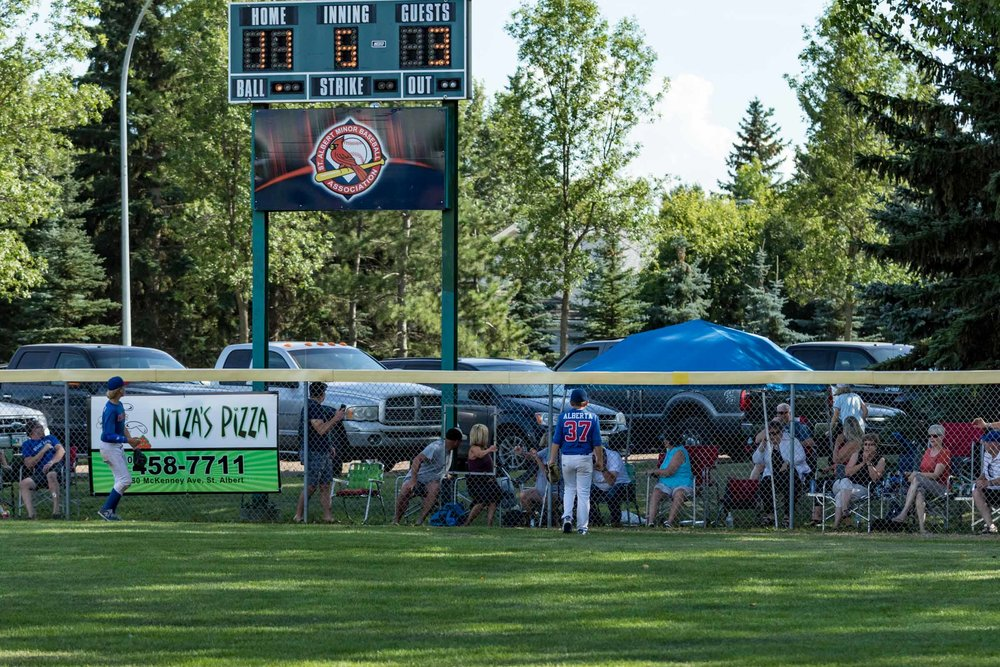 As you can see on the scoreboard the Peewee AA Western Canadian Championship game was a little bit of a runaway. In fact this home run was a walk off mercy win for Winkler (MB) over the Camrose Cougars. The crowd beyond the fence was watching in amazement at the distance and the intrigue to see who's vehicle it would land on | August 14 at Legion Memorial Ballpark, St. Albert