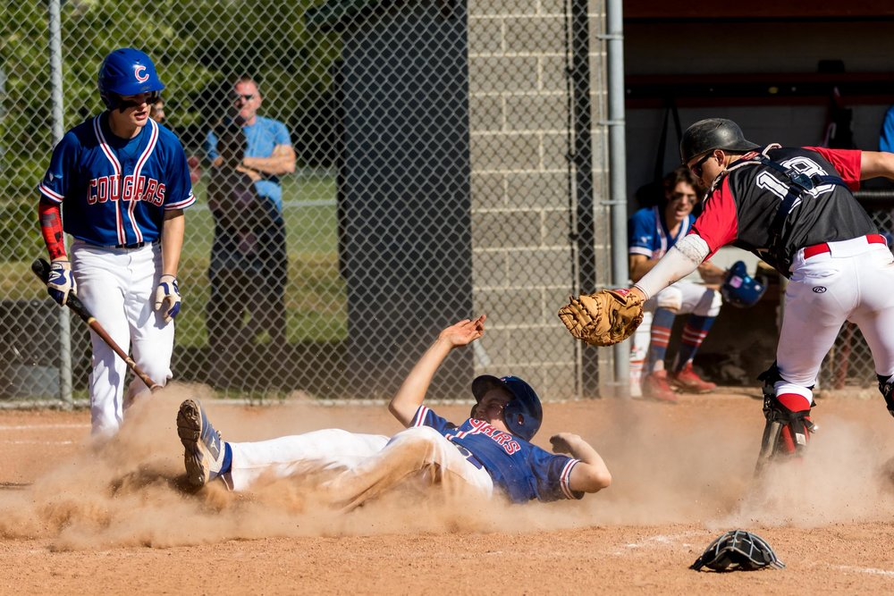 This was the winning run for the Camrose Cougars AA Midget team against the Edmonton Angels in the Midget AA Provincial Tournament. Lying almost completely on his back allowed the Cougars runner to avoid the tag of the Angels catcher | July 29 at Four Seasons Park, Beaumont