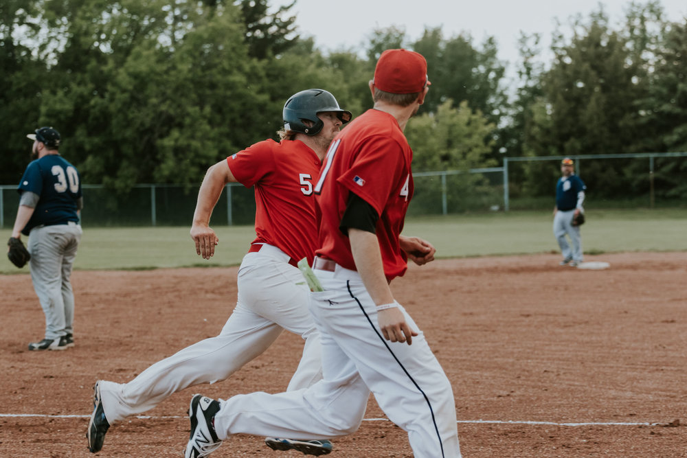 There is nothing like support from a teammate. In this case Camrose Axemen outfielder Blair Mulder (5) gets encouragement all the way down the third base line from reliever and third base coach Kyle Muzechka | June 1 at Archie Jenkins Field, Bon Accord