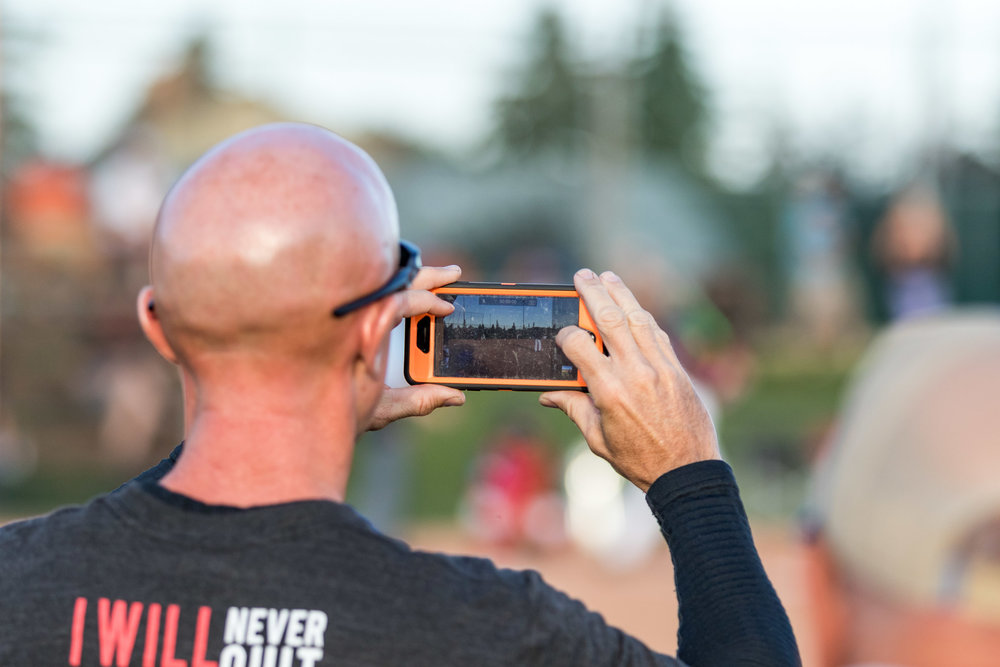A baseball fan gets a video of some baseball action. It doesn't matter what camera a person has, it is all about the moment that they are capturing | August 5 at Rudy Swanson Park, Camrose