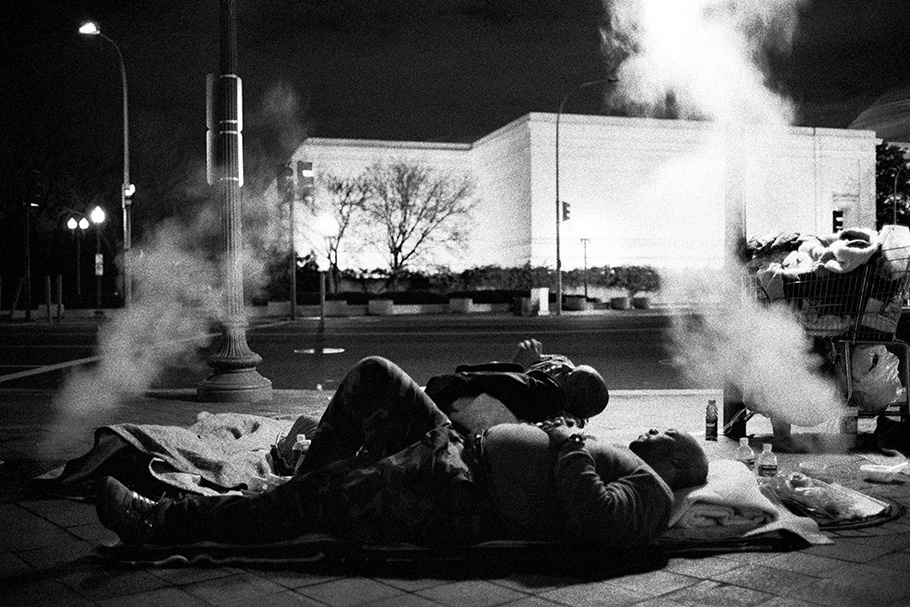 Homeless people sleeping on a Pennsylvania Avenue sidewalk near the National Gallery of Art. They are warmed by the heating vents of large buildings nearby.  August 2003.  © Kike Arnal
