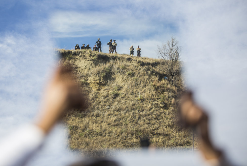 A protester holds up a mirror at the police lining the ridge of Turtle Hill at Standing Rock, N.D. on Nov. 6, 2016 as a way to flash light at the police and as a symbol for them to reflect on themselves and their actions against the protestors.