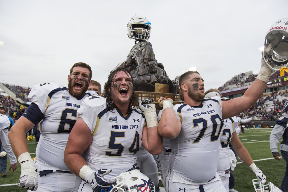 Montana State Bobcat players, Patrick Carroll, left, Monte Folsom, center, and Alex Neale, right, carry The Great Divide Trophy around Washington-Grizzly Stadium for a victory lap after the game on Nov. 19, 2016. The Bobcats won the 116th Brawl of the Wild, 24-17.