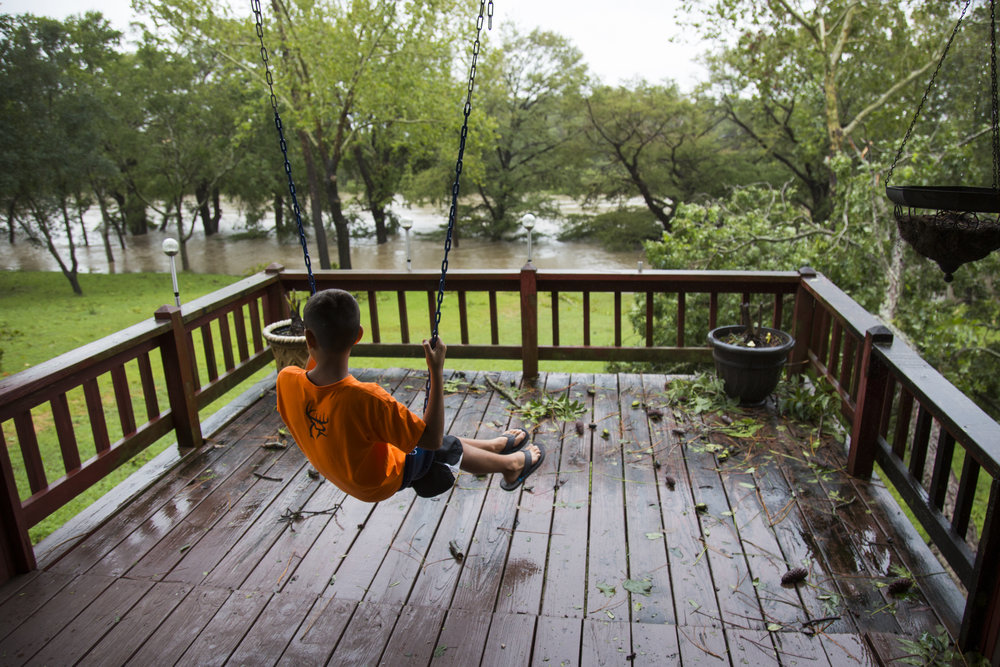 Conner Keeng, 10, swings on his grandfather porch in Cuero, Texas as the Guadalupe River begins to rise in foreground on Aug. 28, 2017. Only days after Hurricane Harvey hit Texas, inland towns such as Cuero were evacuated due to flash flooding caused by the hurricanes record breaking rainfall.