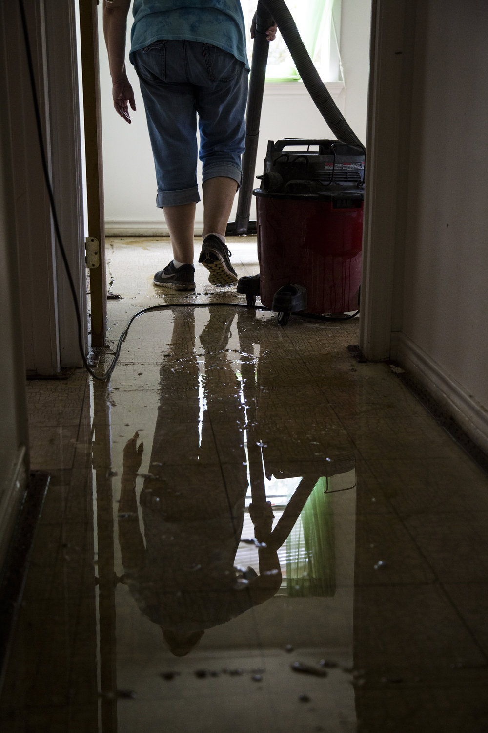 Susie Starkey helps vacuum up leftover floodwater from the Hamilton's home in Greens Addition.