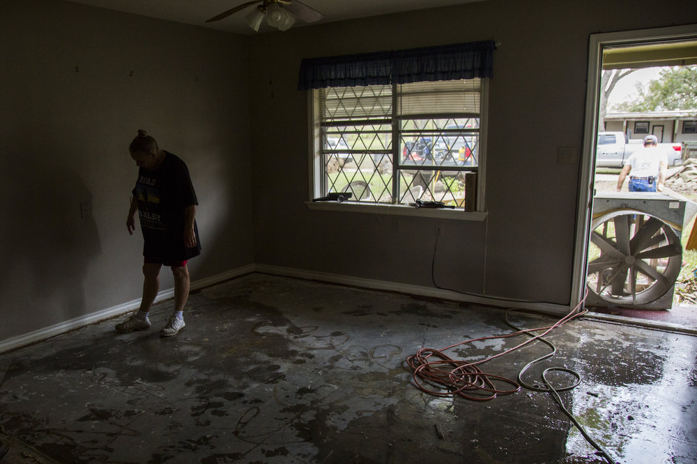 Helena Hamilton, 53, looks at the puddles of water left over after the Guadalupe River flooded her home in Greens Addition.