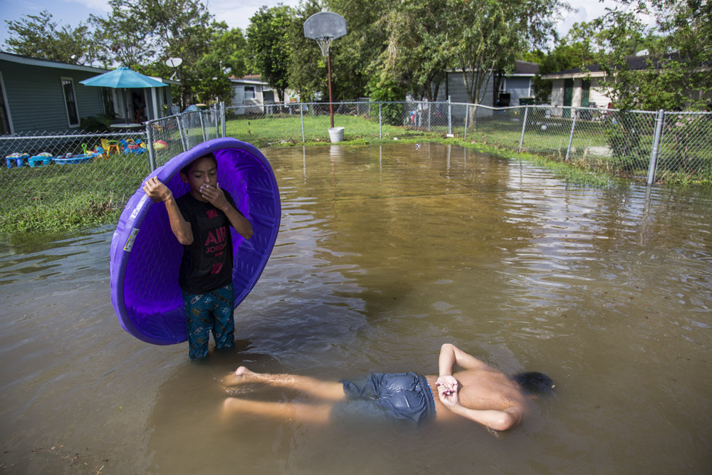 Jeffery Kichen, 9, left, counts in his head to keep track of how long Xavier Salazar, 12, can hold his breath underwater. The city of Victoria, Texas was hit with a rain storm that caused sudden flooding throughout the city due to the already over-saturated ground from Hurricane Harvey.